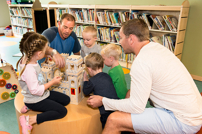 Adults and children play with a castle in a library